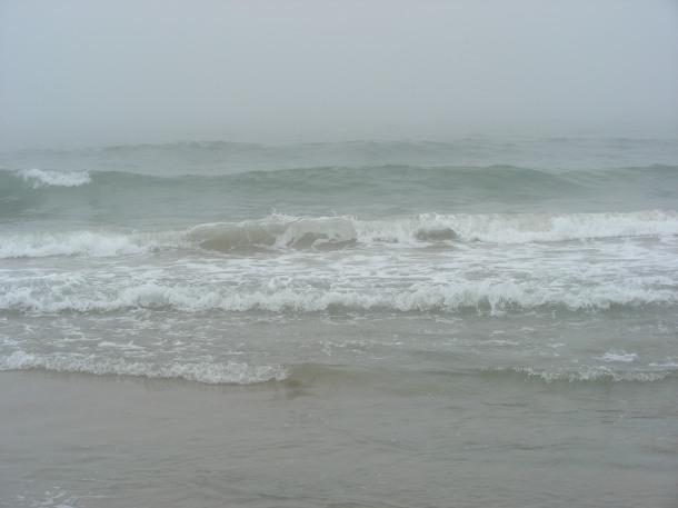 A foggy morning. A train of waves coming ashore.
